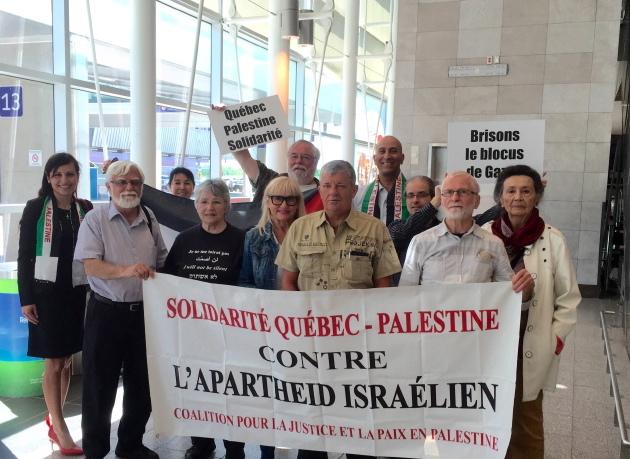 10 personnes derrière Christian Martel à l'aéroport de Québec. Bannière: Solidarité Québec-Palestine contre l'apartheid israélien. Affichette: Brisons le blocus de Gaza.
